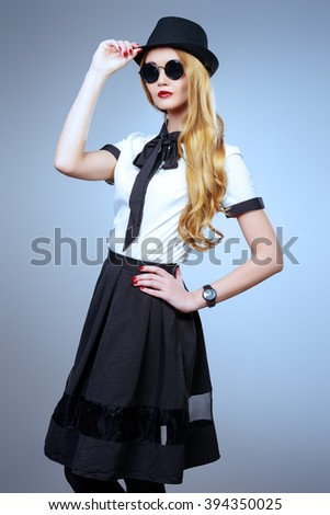 Fashion model posing. Beautiful young woman wearing pretty blouse and skirt. Studio portrait over gray background. - stock photo