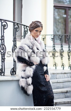 Fashion model posing in a fur coat on a stairs - stock photo