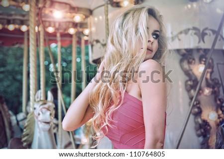 Fashion model posing on carousel - stock photo