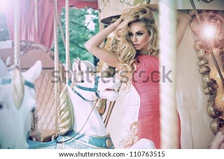 Fashion model posing on carousel in pretty summer dress - stock photo