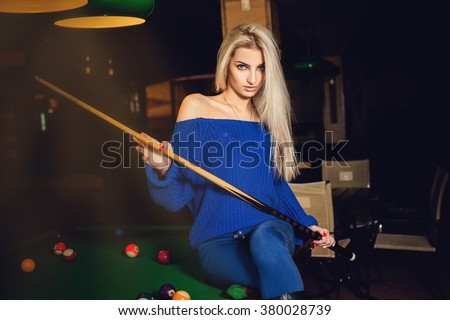 Fashion model posing on pool table with cue in hands. Billiard sport concept. Pool billiard game. American pool billiard. - stock photo