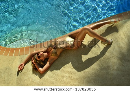 Fashion model posing pretty by swimming pool wearing designers one piece swimsuit and sunglasses - stock photo