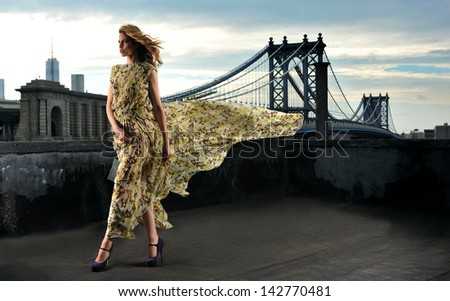 Fashion model posing sexy, wearing long evening dress on rooftop location with metal bridge construction on background - stock photo