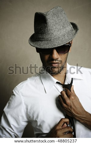 Fashion model shows off his tie, sunglasses and fedora - stock photo