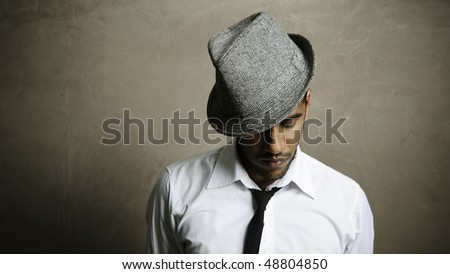 Fashion model takes a moment to think, his eyes downcast - stock photo