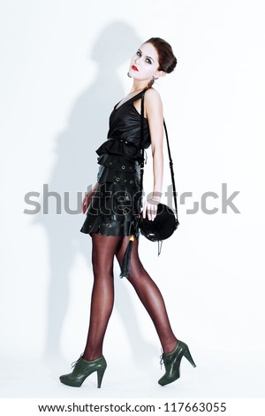 Fashion model walking at white wall - stock photo