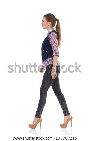 Fashion model walking in high heels. Beautiful girl in high heels walking, Side view. Full length studio shot isolated on white.