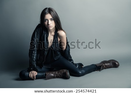 Fashion model wearing leather pants and jacket posing on grey background - stock photo