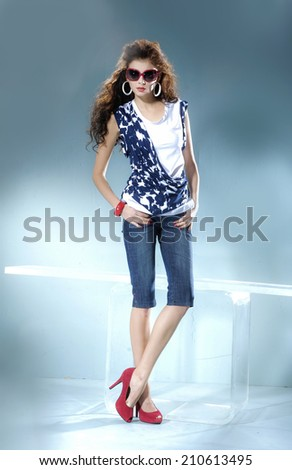 fashion model wearing modern sunglasses posing in light background - stock photo