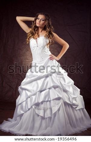 Fashion model wearing wedding dress at brown studio background - stock photo