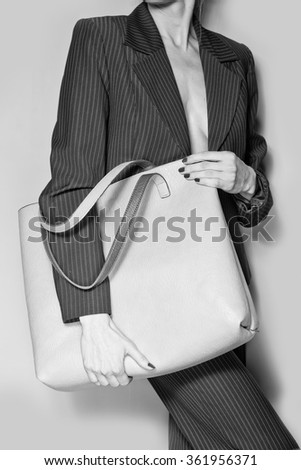 Fashion model with bag. posing in the studio. black and white - stock photo