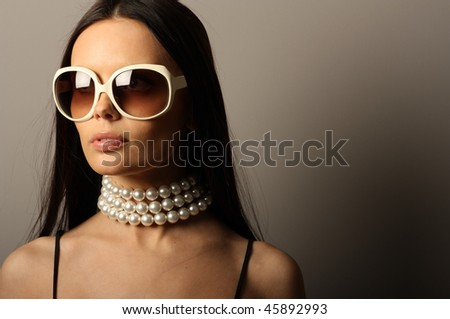 Fashion model with big white sunglasses and pearls necklace. - stock photo