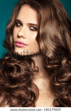 fashion model with bright make-up and curly brunette hair. Smoky eyes