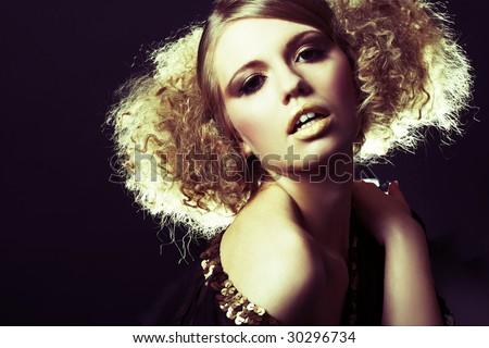 fashion model with curly hair in black tunic in black background - stock photo