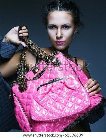 Fashion model with pink bag. posing in the studio - stock photo