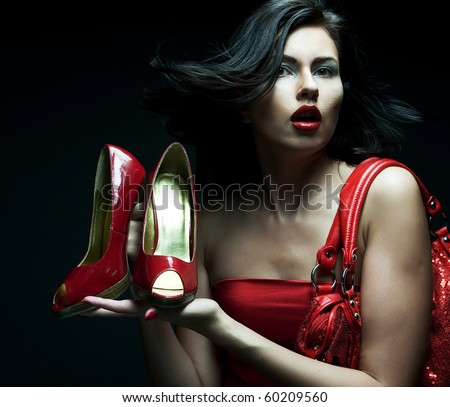 fashion model with red bag and red shoes. on black background. - stock photo