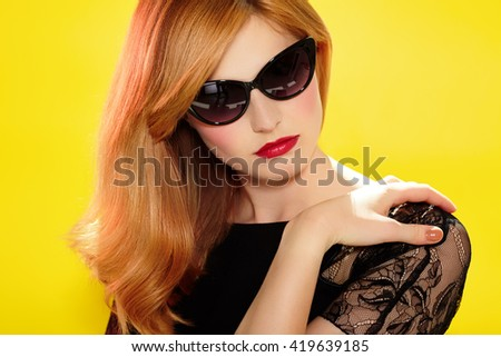 Fashion model with retro sunglasses and red lipstick on yellow background.