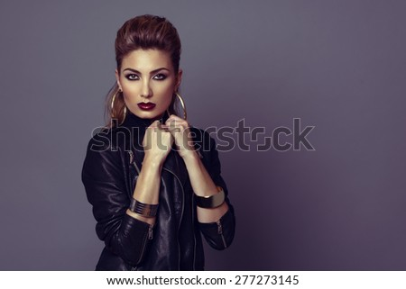 Fashion model with rock style hairstyle and make-up, posing with leather jacket.