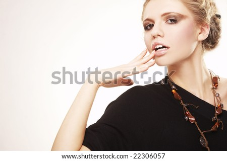 Fashion model with strong makeup posing on white background - stock photo