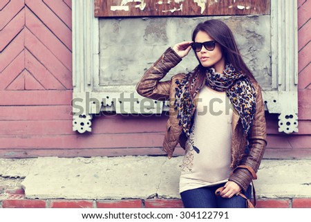 Fashion model with sunglasses, leather jacket, scarf, and handbag - stock photo