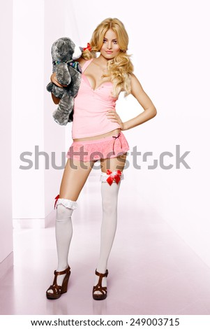 Fashion model with teddy bear. Design of toy is altered.  - stock photo