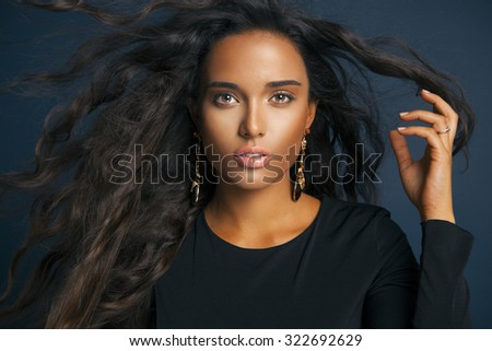 Fashion model with wavy hairstyle. portrait of young woman with makeup and tanned skin. Toned in warm colors. Studio shot, horizontal - stock photo