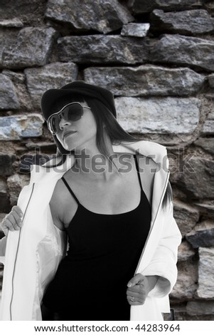 Fashion model with white jacket against a rough pattern of a historic brick wall