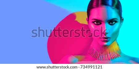 Fashion model woman in colorful bright lights posing, portrait of beautiful sexy girl with trendy make-up. Art design, colorful make up. Over colourful vivid background. Night club dancer