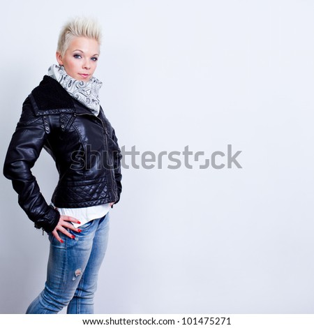 fashion model woman posing in blue jeans and black leather jacket on gray background - studio shot - stock photo