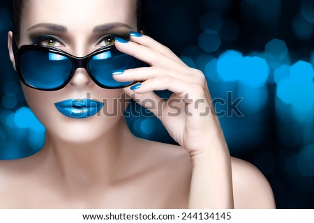 Fashion model woman with stylish oversized sunglasses looking at camera. Colorful makeup and manicure. Beauty and fashion concept. High fashion portrait over blue abstract background with copy space. - stock photo