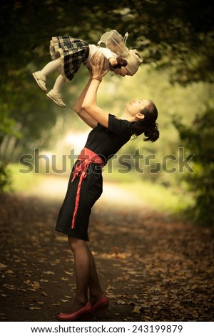 Fashion Mom throwing up adorable toddler little girl. Park. Autumn. Magic beauty natural back light - stock photo