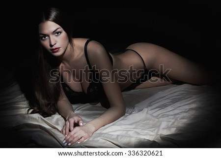 fashion monochrome portrait of sexy woman posing in bed. Hot woman with perfect slim body in underwear.Lady lying in bed - stock photo