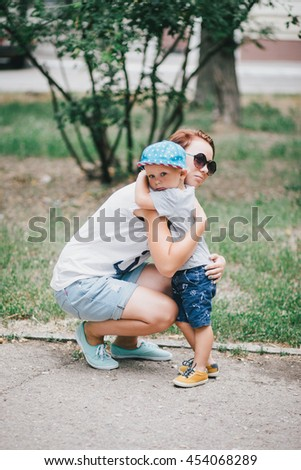 Fashion mother and her little son posing in a park