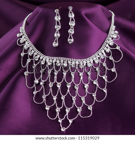 fashion necklace and earrings on purple silk background - stock photo