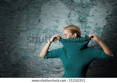 fashion ninja woman in blue dress near old blue wall - stock photo