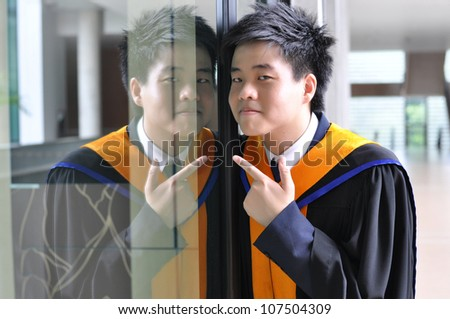Fashion of graduate in thailand ,graduation boy holding his master's degree. - stock photo