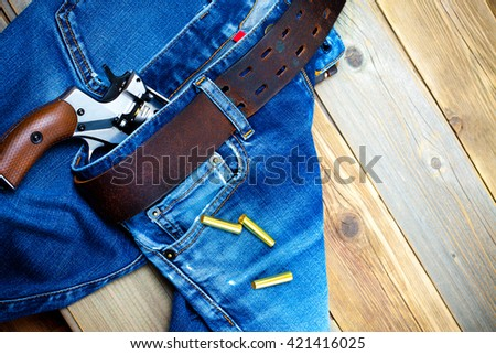 fashion old blue jeans with a leather belt and vintage revolver with cartridges. on a wooden textured background - stock photo