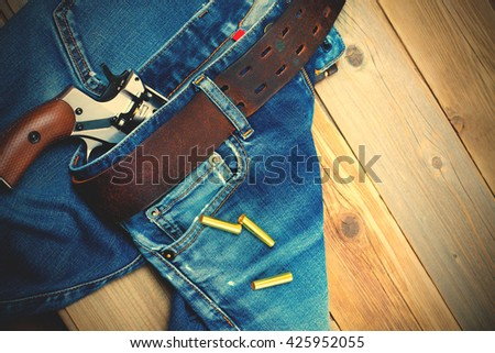 fashion old blue jeans with a leather belt and vintage revolver with cartridges. on a wooden textured background. instagram image filter retro style - stock photo