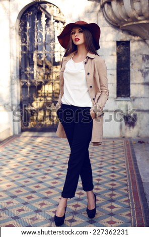fashion outdoor photo of beautiful elegant woman with dark straight hair wearing elegant coat and hat,posing in palace