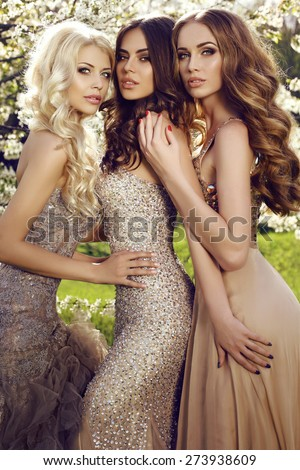 fashion outdoor photo of beautiful gorgeous women in luxurious dresses  posing in spring blossom garden - stock photo