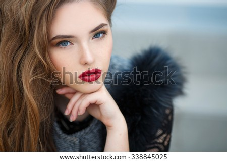 fashion outdoor photo of beautiful lady with dark hair wearing elegant coat,leather gloves and felt hat,posing in autumn park. Beautiful fashionable woman standing on the city street. - stock photo
