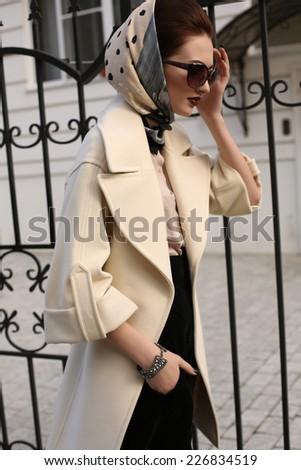 fashion outdoor photo of beautiful ladylike woman wearing elegant wool coat and silk scarf on her head, walking along the street - stock photo