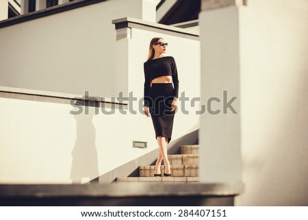 fashion outdoor photo of beautiful ladylike woman with long hair wearing elegant pencil skirt and posing in city - stock photo