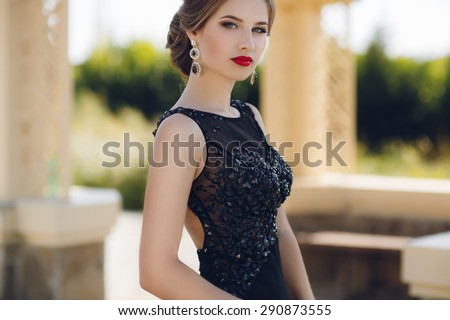 Fashion outdoor photo of beautiful sensual woman in luxurious sequin dress posing in summer park. fashion photo of beautiful tender woman with dark hair in elegant  dress posing in summer garden - stock photo
