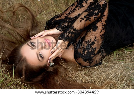 Fashion outdoor photo of beautiful sensual woman with dark hair and tanned body,wearing elegant clothes,posing in summer field - stock photo