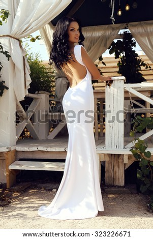 fashion outdoor photo of beautiful sensual woman with dark hair in elegant white dress with open back  - stock photo