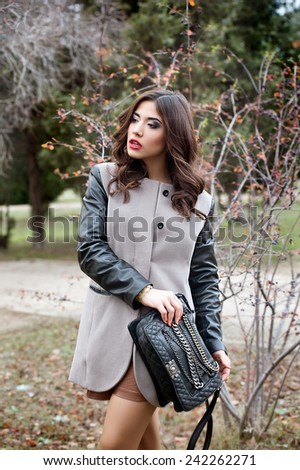 fashion outdoor photo of beautiful sensual woman with dark hair wearing luxurious coat - stock photo