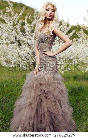 fashion outdoor photo of beautiful sensual woman with long blond hair in luxurious sequin dress posing in spring blossom garden