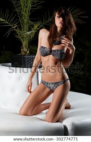 Fashion outdoor photo of beautiful sexy girl  in elegant bikini posing a swimming pool. - stock photo