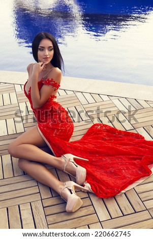 fashion outdoor photo of beautiful sexy girl with black hair in luxurious red lace dress and beige shoes posing beside a swimming pool - stock photo